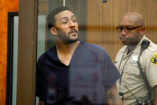 Former NFL football player Kellen Winslow Jr., center, looks through protective glass during his arraignment Friday, June 15, 2018, in Vista, Calif. (Hayne Palmour/San Diego Union-Tribune via AP, Pool)