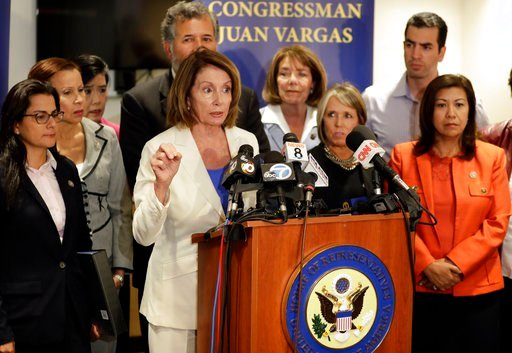 House Minority Leader Nancy Pelosi, D-Calif., at podium, speaks in front of members of the Congressional Hispanic Caucus during a visit to the border Monday, June 18, 2018, in San Diego. The members of congress spoke about their visit to area immigration
