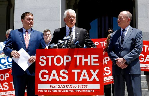 Republican gubernatorial candidate John Cox, center, blasts a recent gas tax increase during a news conference Monday, June 18, 2018, in Sacramento, Calif.  (AP Photo/Rich Pedroncelli)