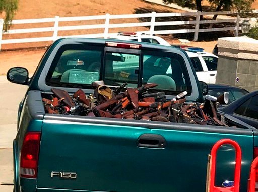 This June 2018 photo provided by the Los Angeles County Sheriff's Department shows over 550 firearms that Los Angeles County sheriff's deputies and state and federal investigators seized at homes in Agua Dulce, Calif. (Los Angeles County Sheriff's Departm