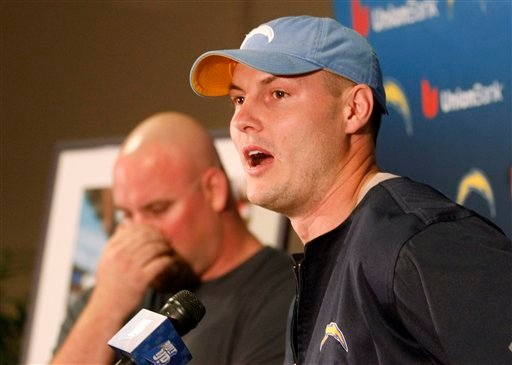 San Diego Chargers quarterback Philip Rivers talks about lineman Chris Dielman, rear, during a news conference in which Dielman announced his retirement from NFL football, Thursday, March 1, 2012 in San Diego.