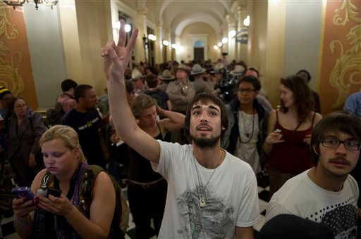 A University of California Santa Cruz Student who identified himself as Tyler, gives a peace sign as college students andothers occupied the Capitol Rotunda on Monday, March 5, 2012, in Sacramento, Calif.