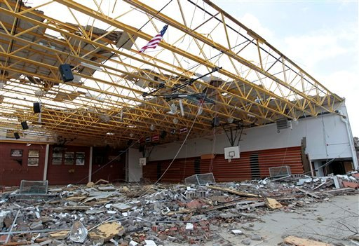 FILE - This March 3, 2012 file photo shows an American flag flying over the damaged gym at Henryville High School in Henryville, Ind. (AP Photo/Michael Conroy)