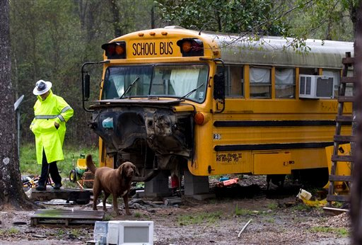 A Montgomery Count sheriff's deputy walks away from an old school bus where two children were found living on their own Wednesday, March 7, 2012, in Spendora, Texas. (AP Photo/Brett Coomer, Houston Chronicle)