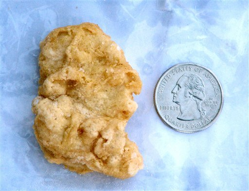 FILE - In this Feb. 21, 2012 file photo, a McDonald's Chicken McNugget found by Rebekah Speight of Dakota City, which she believes resembles President George Washington is placed next to a U.S. quarter dollar bearing the image of the president.