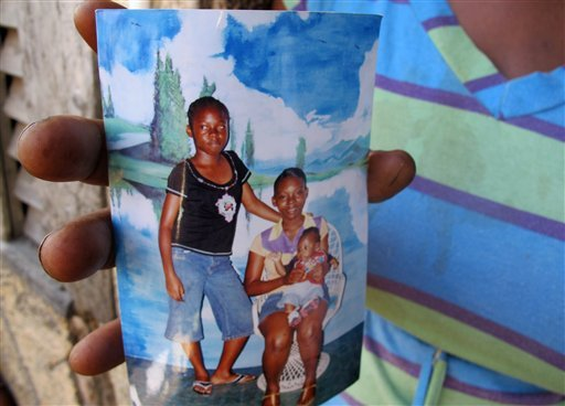 Beverly Kennedy holds an old photograph of her slain daughter, Nicketa Cameron, standing left, in the Denham Town slum in Kingston, Jamaica, Thursday March 8, 2012.