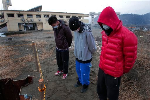 High-school students mourn the victims of the March 11, 2011 earthquake and tsunami, in Rikuzentakata, Iwate Prefecture, northeastern Japan, Sunday, March 11, 2012. (AP)