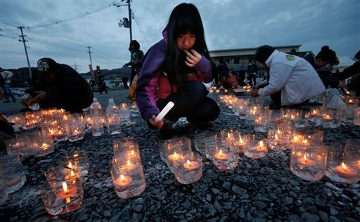 A girl lights candles in front of a temporary shopping complex in the earthquake and tsunami-devastated city of Kesennuma, Iwate prefecture, northeastern Japan, Sunday, March 11 2012, to mark the first anniversary of the massive disaster. (AP)