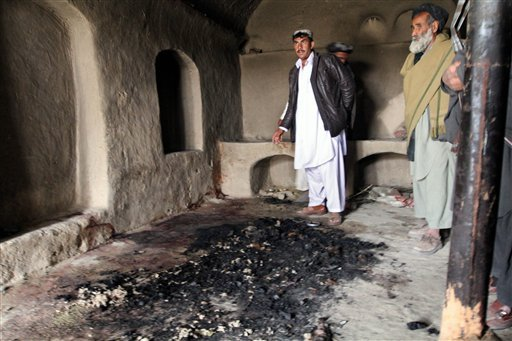 In this Sunday, March 11, 2012 photo, men stand next to blood stains and charred remains inside a home where witnesses say Afghans were killed by a U.S. soldier in Panjwai, Kandahar province south of Kabul, Afghanistan, on Sunday.