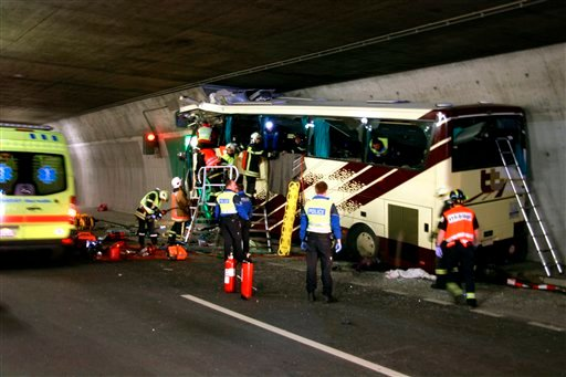 Rescuers and police work amid the wreckage of a tourist bus from Belgium at the accident site in a tunnel of the A9 highway near Sierre, western Switzerland, early Wednesday, March 14, 2012. (AP Photo/KANTONSPOLIZEI WALLIS/POLICE OF VALAIS, Handout)