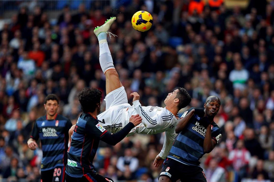 In this photo Real Madrid's Cristiano Ronaldo tries to score in between opposition players during a Spanish La Liga soccer match between Real Madrid and Granada at the Santiago Bernabeu stadium in Madrid, Spain. (AP Photo/Andres Kudacki)