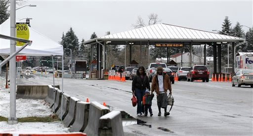 Pedestrians walk to a bus stop near a gate at Joint Base Lewis McChord, Tuesday, March 13, 2012, in Washington state.