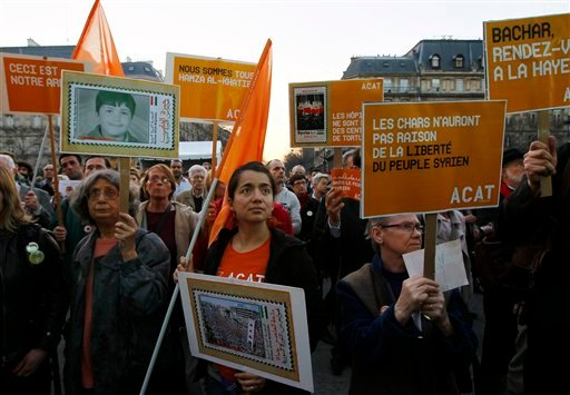 "Protesters holding placards reading 'Bachar Meet you in The Hague"" referring to Syria's President Bashar Assad and the International Criminal Court of The Hague during a rallye to support the Syrian people in Paris. (AP Photo/Francois Mori)"