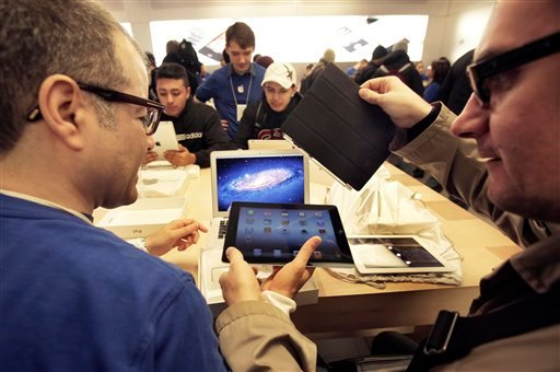 An Apple employee, left, assists a man with his new iPad at Apple's flagshop store, in New York, Friday, March 16, 2012.
