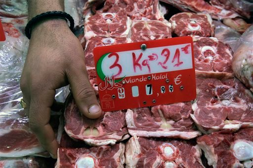 In this photo taken Friday, March 9, 2012, a butcher arranges halal meat at a butcher shop in Paris. (AP)