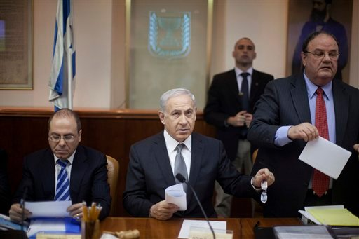 Israeli Prime Minister Benjamin Netanyahu, center, heads the weekly cabinet meeting in his offices in Jerusalem, Sunday, March 18, 2012. Sitting left is deputy premier Silvan Shalom, man at right is unidentified. (AP Photo/Uriel Sinai, Pool)