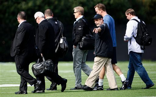 NFL quarterback Peyton Manning, second from right at rear, walks across a football practice field with Denver Broncos executive John Elway, fourth from left, March 16, 2012, at Duke University in Durham, N.C. (AP Photo/The News & Observer, Travis Long)