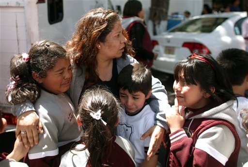 A woman comforts her crying children outside a school in the Roma neighborhood after a earthquake was felt in Mexico City, Tuesday March 20, 2012.