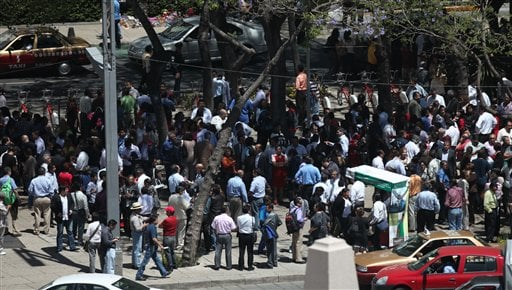 Workers and residents gather at the Angel de la Independencia square after evacuating buildings during a earthquake felt in Mexico City Tuesday March 20, 2012. (AP Photo/Dario Lopez-Mills)
