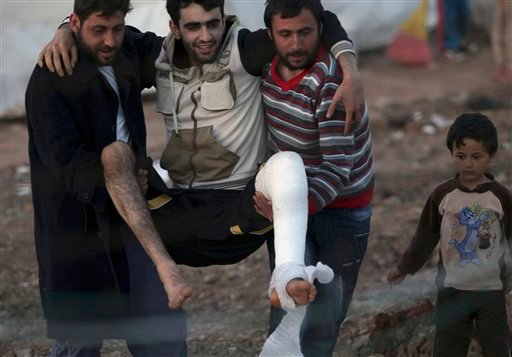 Friends carry an injured Syrian refugee inside their camp in Reyhanli, Turkey, Tuesday, March 20, 2012. The number of Syrian refugees in Turkey is now about 17,000.(AP Photo/Burhan Ozbilici)