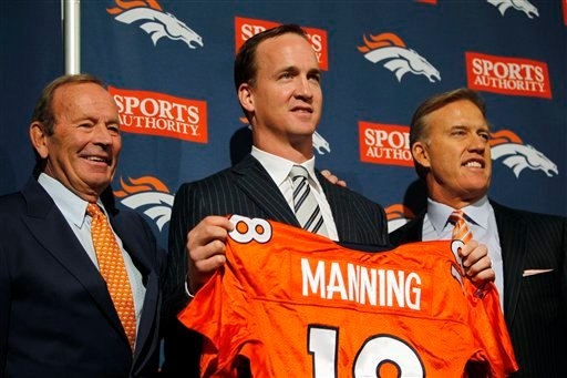 From left, Denver Broncos owner Pat Bowlen, newly-signed quarterback Peyton Manning and executive vice president of football operations John Elway pose for photos during an NFL football news conference at the team's headquarters in Englewood, Colo.