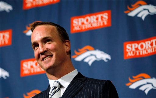 New Denver Broncos quarterback Peyton Manning jokes with reporters during an NFL football news conference.