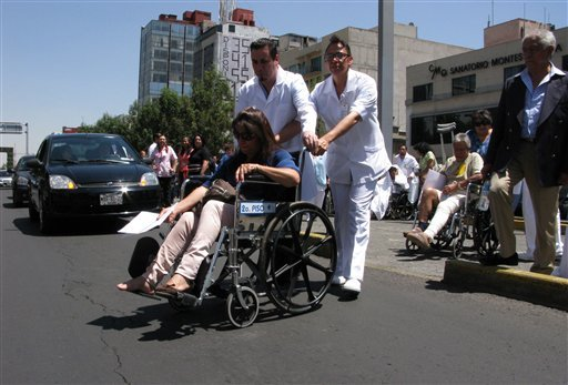 Patients are evacuated in wheelchairs from the Hospital de Chalpultepec after an earthquake was felt in Mexico City, Tuesday March 20, 2012. (AP Photo/Marco Ugarte)