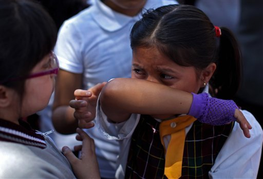 A child cries after she and her classmates were evacuated from her school in the Roma neighborhood when an earthquake was felt in Mexico City, Tuesday March 20, 2012. (AP Photo/Alexandre Meneghini)