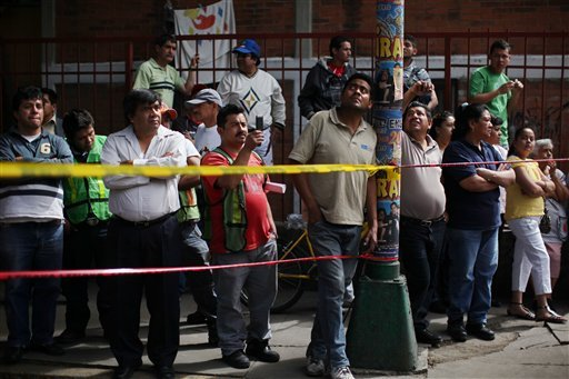 People watch firefighters working to remove a cement beam that fell from a bridge onto a public mini-bus after an earthquake was felt in Mexico City, Tuesday March 20, 2012. (AP Photo/Alexandre Meneghini)