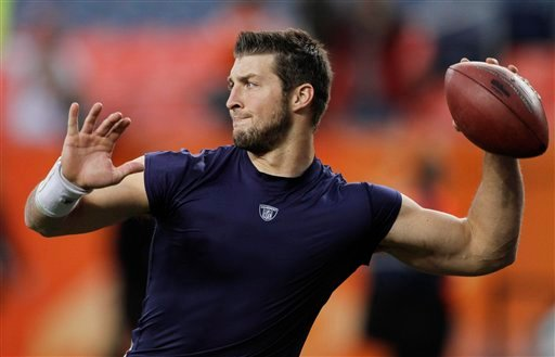 FILE - In this Nov. 17, 2011 file photo, Denver Broncos quarterback Tim Tebow warms up before playing the New York Jets in an NFL football game, in Denver. Tebow has been traded from the Denver Broncos to the New York Jets. (AP Photo/Barry Gutierrez)