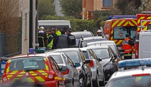 Police officers and firefighters stand next to the building where the suspected killer is holed-up in Toulouse Wednesday March 21, 2012.