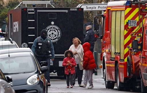 A woman and children are escorted by a police officer near a building where the chief suspect in an al-Qaeda-linked killing spree is holed up in an apartment in Toulouse, France Thursday March 22, 2012. (AP Photo/Remy de la Mauviniere)