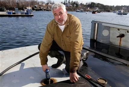 In this March 20, 2012 photo, third generation lobsterman Craig Rogers fuels up his lobster boat at Mackeral Cove in Bailey Island, Maine. Rogers, of Harpswell, said high fuel prices are the biggest concern of lobstermen.(AP Photo/Pat Wellenbach)