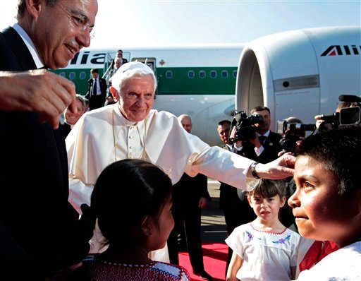 Mexico's President Felipe Calderon, left, looks on as Pope Benedict XVI is greeted by children at the airport in Silao, Mexico, Friday March 23, 2012. (AP Photo/Gregorio Borgia)