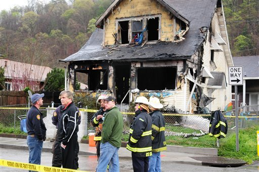 In this photo provided by Jerry Waters, Mayor Danny Jones and Charleston, W.Va., firefighters look over the scene of a house fire on Saturday, March 24, 2012 in Charleston. (AP Photo/Jerry Waters)