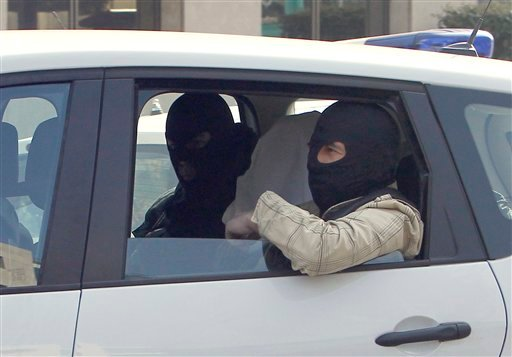 An unidentified man with his head covered, believed to be Abdelkader Merah or his companion, sits between masked police officers as they head to the French police's anti-terrorist headquarters in Levallois-Perret. (AP Photo/Christophe Ena)