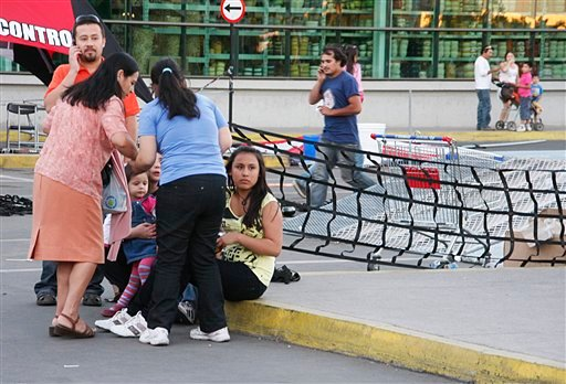 People gather outside a supermarket after an earthquake was felt in Talca, Chile, Sunday, March 25, 2012. (AP Photo/Fabian Suazo)