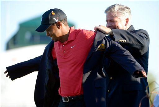 Tiger Woods, left, is presented the jacket for winning the Arnold Palmer Invitational golf tournament at Bay Hill by tournament chairman Don Oehlrich in Orlando, Fla., Sunday, March 25, 2012. (AP Photo/Phelan M. Ebenhack)