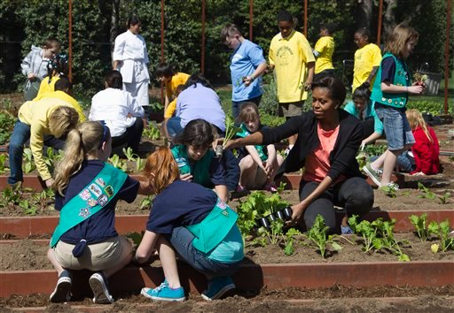 First lady Michelle Obama plants vegetable seedlings with Girl Scouts, foreground, from left, Emma Vonderlinn, Emily Burnham, of Fairport N.Y., and Gia Muto, during a spring planting of the White House kitchen garden. (AP Photo/Manuel Balce Ceneta)