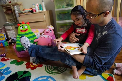 Christopher Astacio reads with his daughter Cristina, 2, recently diagnosed with a mild form of autism, in her bedroom on Wednesday, March 28, 2012 in New York. (AP Photo/Bebeto Matthews)