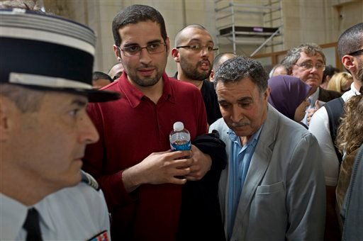 French nuclear physicist Adlene Hicheur's brother Halim Hicheur, center, and his father, right, wait prior to entering a Paris courthouse Thursday March 29, 2012 where Adlene Hicheur goes on trial. (AP Photo/Thibault Camus)