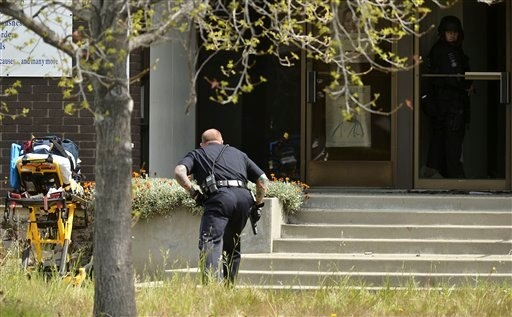 An Oakland police officer approaches the entrance to Oikos University in Oakland, Calif., Monday, April 2, 2012. (AP Photo/Noah Berger)