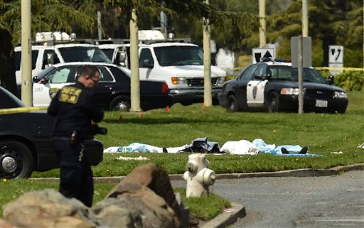 Bodies lie covered on the grass as Oakland Police work near Oikos University in Oakland, Calif., Monday, April 2, 2012. (AP Photo/Noah Berger)