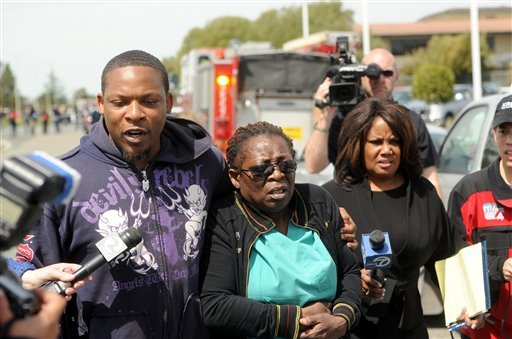 Marilyn Daniels, center, an employee at Oikos University, is comforted near the school in Oakland, Calif., following a shooting on Monday, April 2, 2012. (AP)