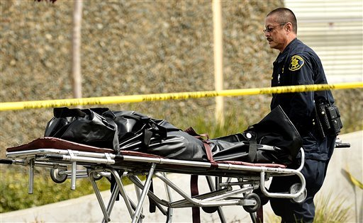 A sheriff's deputy removes a body from outside Oikos University in Oakland, Calif., Monday, April 2, 2012. (AP)