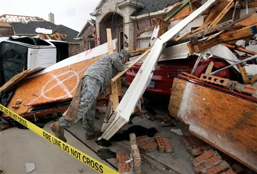 Texas Army National Guard Cpl. Brock Fischer of Charlie Troop, 3-124 Cav., searches a vehicle in front of a tornado damaged home Tuesday, April 3, 2012, in Forney, Texas. (AP Photo/Tony Gutierrez)