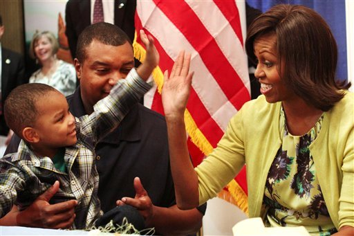 First lady Michelle Obama gets a high five with Eun White, seated with his father, Army Maj. Eunotchol White, during the first lady's visit to Fisher House at Walter Reed National Military Medical Center in Bethesda, Md., Wednesday, April 4, 2012.
