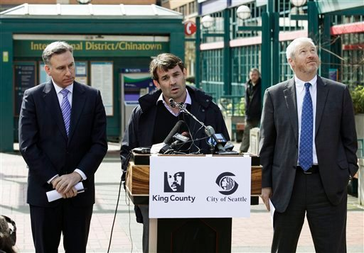 King County Executive Dow Constantine, left, looks on as Chris Hansen, center, the venture capitalist who wants to build a new sports arena in Seattle, talks to reporters. (AP Photo/Ted S. Warren)