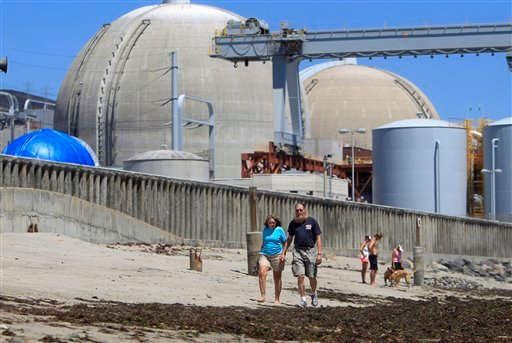 This file photo taken June 30, 2011 shows beach-goers walking on the sand near the San Onofre nuclear power plant in San Clemente , Calif.