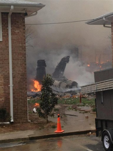 The burning fuselage of an F/A-18 Hornet lies smoldering after crashing into a residential building in Virginia Beach, Va.